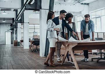 appassionato, circa, loro, project., gruppo, di, giovane, persone affari, lavorare insieme, in, creativo, ufficio, mentre, standing, appresso, il, scrivania legno
