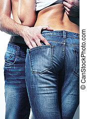 Appeal - Vertical shot of a seductive couple wearing jeans...