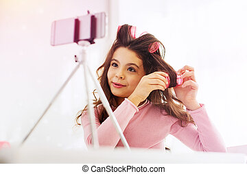 Appealing pleasant girl having video chat with her mother while curling hair at home