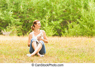 Appealing woman sitting on grass with cat on her knees