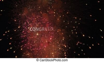Appearing white text Congratulations on the background of the Colored firework lights exploding closeup. Dazzling fireworks on black night sky. Festive, winner and celebration concept.