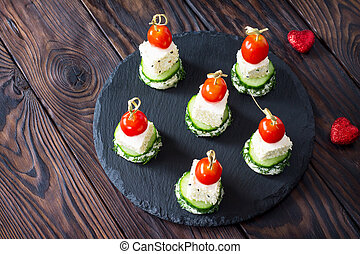 Appetizer canape with white bread, feta cheese, cucumber and cherry tomatoes on a wooden table.