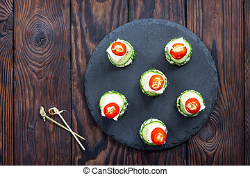 Appetizer canape with white bread, feta cheese, cucumber and cherry tomatoes on a wooden table. Top view.