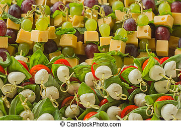 appetizer cheese with white and red grapes on bamboo skewers