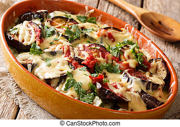 Appetizer from baked eggplants with tomatoes, herbs and cheese close-up. horizontal