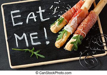 Appetizer. - Grissini bread sticks with prosciutto ham,...