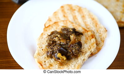 appetizer of cooked eggplant with vegetables on bread -...