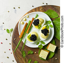 Appetizer of eggs, white sauce and black caviar. Layout on a wooden background with spices and herbs.