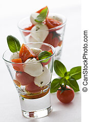 Sliced tomato and mozzarella with basil in glass close up