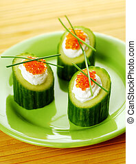 Appetizers with red caviar and a cucumber