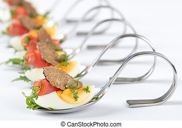 Truffle appetizers with egg, ham rolls, capers and cress on party spoons