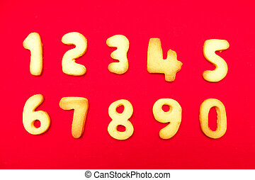 Appetizing cookies in shape numerals on the isolated red...