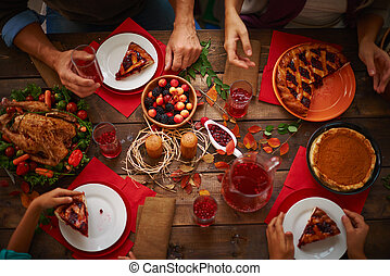 People eating a pie and drinking cranberry compote