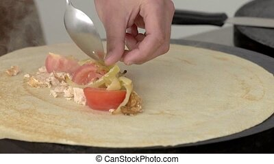 Appetizing filling for pancakes is laid out on a pancake in slow motion