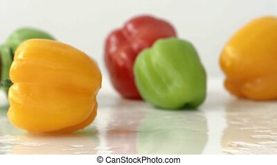 Appetizing fresh Bulgarian pepper spins on a wet surface in...