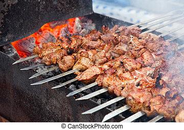 Appetizing fresh meat shish kebab (shashlik) prepared on a grill wood coal, outdor
