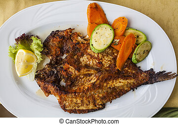 Appetizing grilled fish with vegetables and lemon.