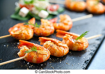Appetizing grilled prawns on skewer. - Extreme close up of...