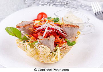 Appetizing meat cut with slices of fresh vegetables.