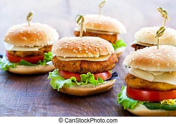 Appetizing mini chicken burgers on wooden surface. - Macro...