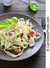 appetizing pasta with mussels and squid, food closeup
