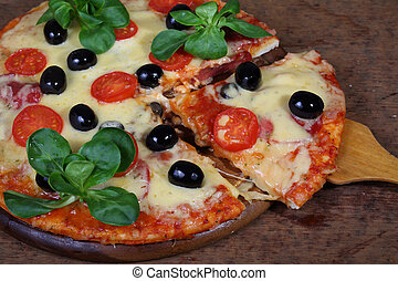 Appetizing pizza from a salami, a mozzarella, olives and tomatoe
