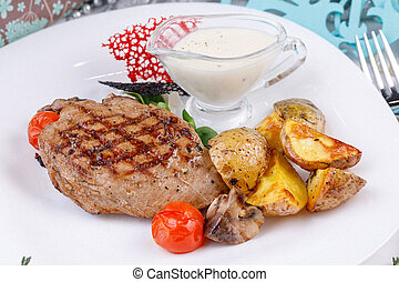 Appetizing pork steak with a garnish of young potatoes.