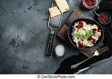 Appetizing ravioli with tomato sauce, cheese and basil with basil parmesan and tomatoe in black bowl , on gray background , top view flat lay , with copyspace and space for text