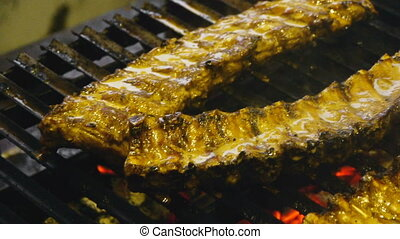 Appetizing ribs on the grill, cooking barbecue meat, juicy lamb ribs with grilled crust on the grill, close-up