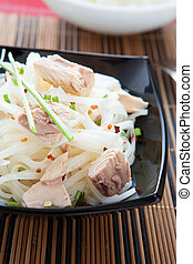 appetizing rice noodles with chunks of tuna in a black bowl