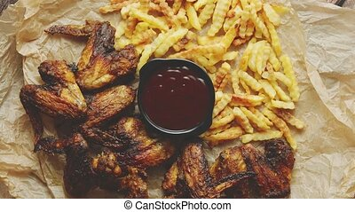 Appetizing roasted chicken wings and french fries with ...