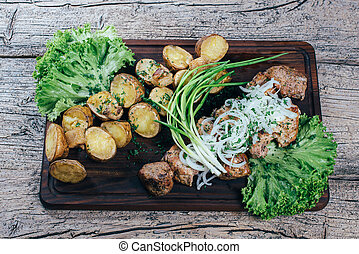 Appetizing roasted pork pieces on the grill, presented on a wooden board, along with leaves of green salad and potatoes