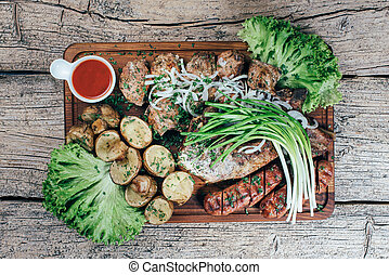 Appetizing roasted pork pieces on the grill, presented on a wooden board, along with leaves of green salad and potatoes with tomato sauce
