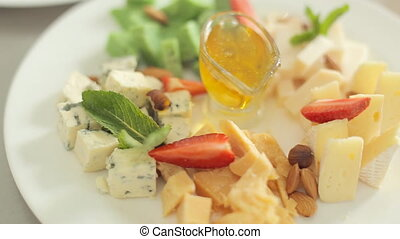 Appetizing sliced elite cheese with mint, nuts and honey -...