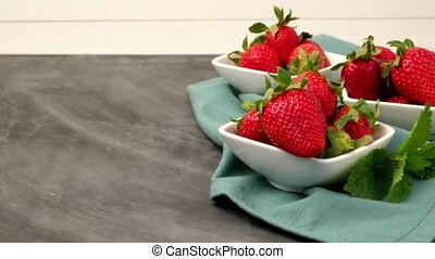 Appetizing strawberry in the bowl on a black slate table...