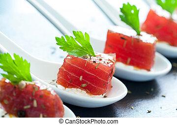 Macro close up of appetizing tuna morsel on ceramic spoons. Row of multiple tuna starters.