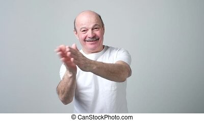 Applauding, clapping senior caucasian man. He is delighted...