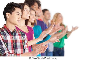 applause., gruppo, di, allegro, giovane, multi-etnico, persone, standing, fila, e, battimano, a, qualcuno, mentre, standing, isolato, bianco
