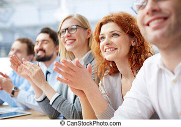 Photo of happy business people applauding at conference, focus on smiling girl