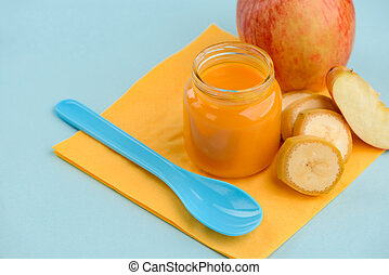 Apple and banana mix puree, spoon and fruits
