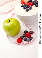 Apple and bowl of berries cream and a tape measure