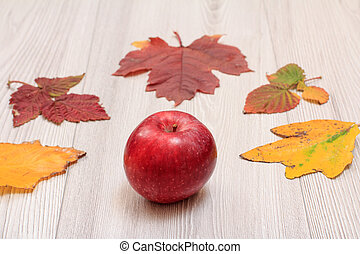Apple and dry leaves on wooden boards. An autumn still llife.