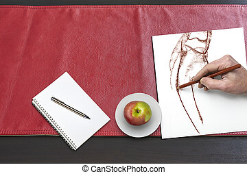 Apple and hand drawing on Red leather tablecloth