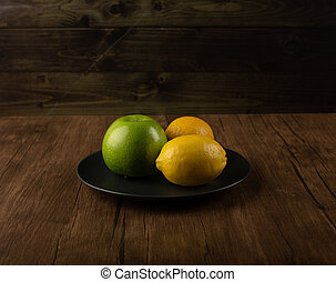 Apple and lemons on a wooden table