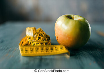 Apple and measuring tape, weight loss diet concept