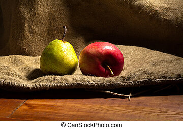 Apple and pear on a wooden background.