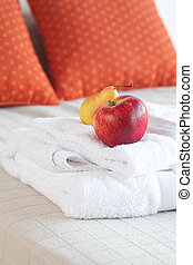 apple and pear on towels on the bed with two pillows