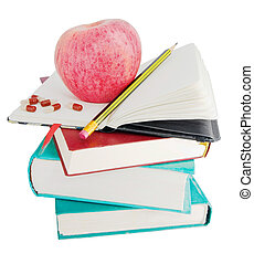 Apple and pills on big pile of books