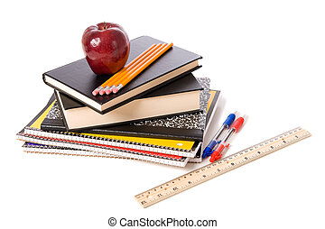 A group of assorted school supplies on a white background with books, pencils, a ruler, notebooks, and ann apple