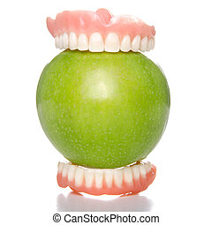 Apple bite - False teeth having a big bite into a green...